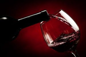 Pouring red wine in wine glass, red background