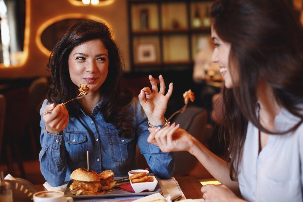two women eating burgers and fries in a restaurant