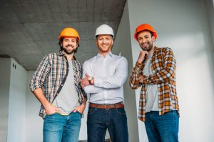 Group of men waering hard hats and smiling