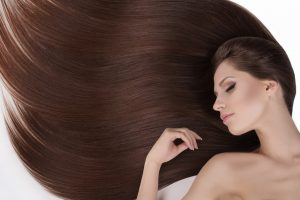 Woman with beautiful hair keeping her eyes closed while isolated on white