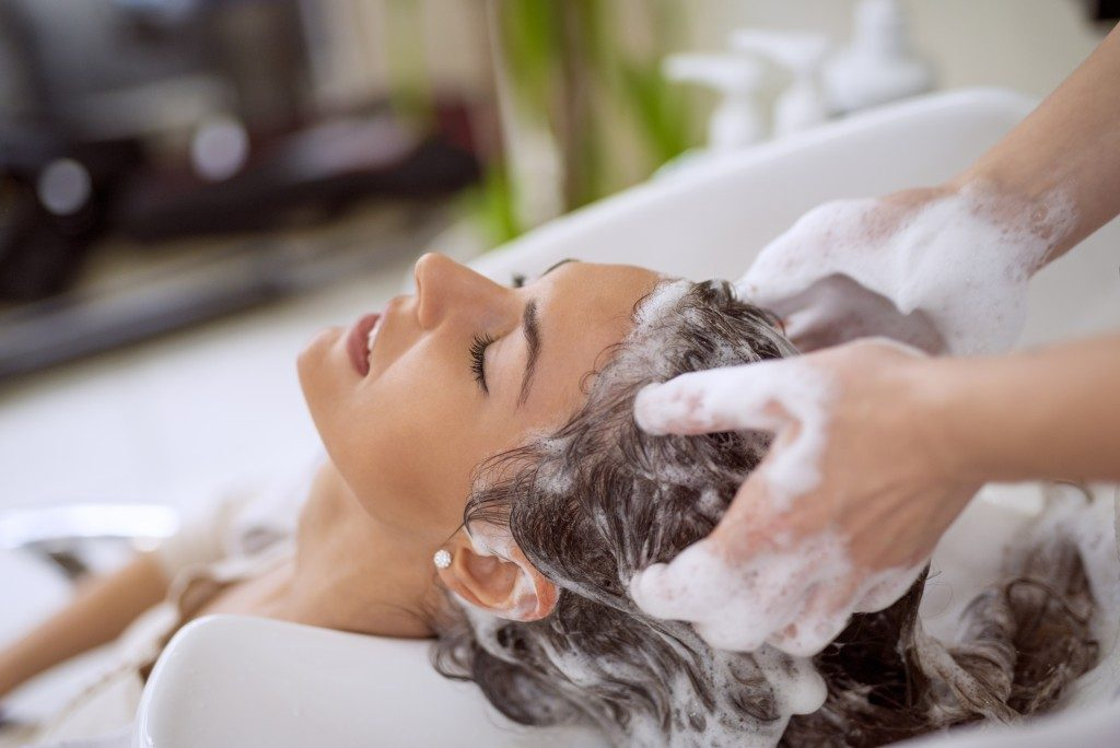 woman's hair being wash in a salon