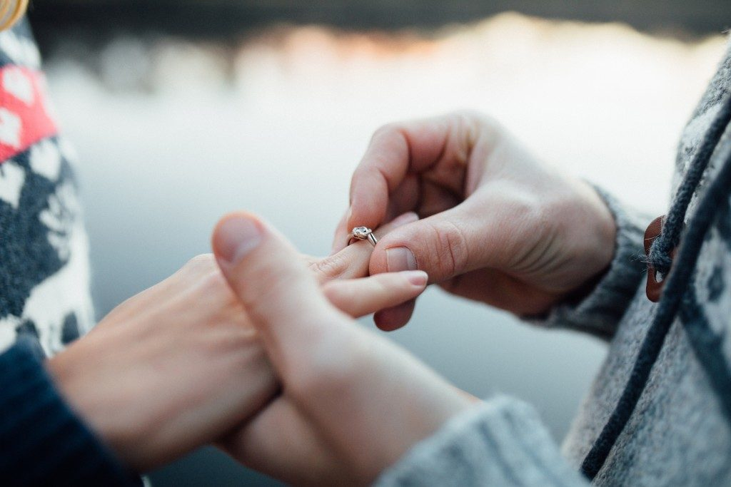 Man putting engagement silver ring on woman's hand, outdoor. Sea or river background