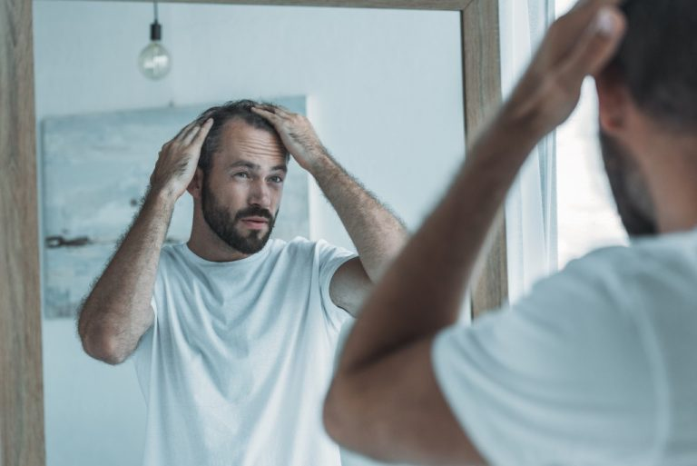 Man looking at his hair in the mirror