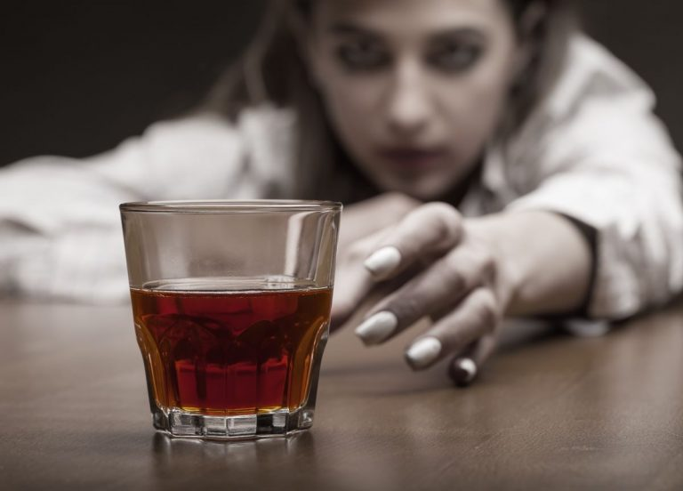 woman reaching for glass with alcohol