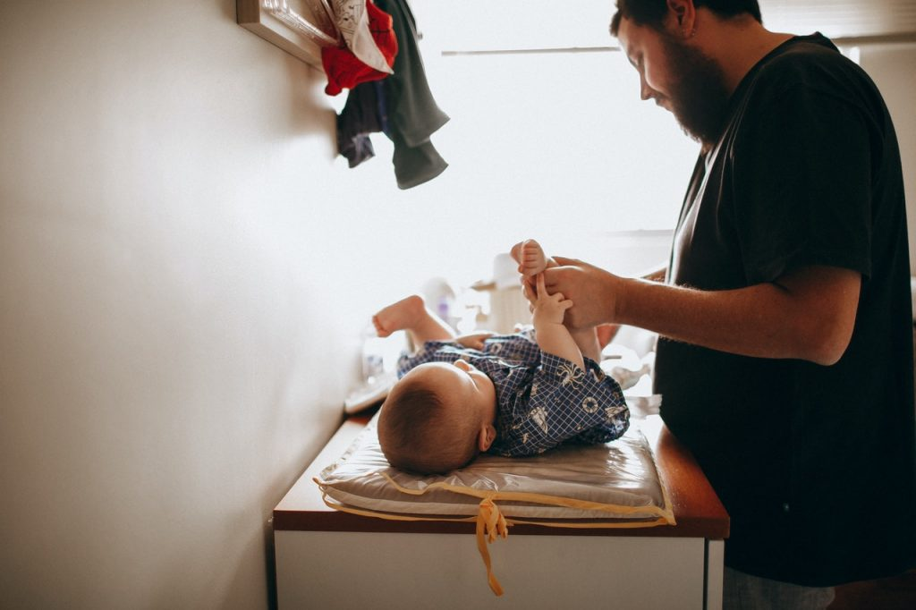 man changing diaper of baby